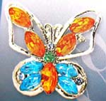 Ladies brooch wear accessory distribution manufacturer. Silver plated butterfly pin with cz gems in wings and in body along with an emerald green rhinestone in center